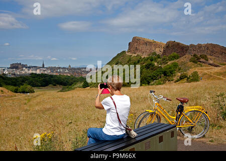 Edinburgh, Scotland, UK. 19 July 2018, UK weather, Edinburgh Holyrood Park, Scotland, with castle and city in the background  woman takes mobile phone photograph and enjoys 20 degrees of sunny weather in the morning with expected cloud and rain much later in the day. - Stock Photo