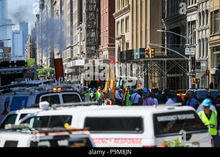 New York, USA. 19th July, 2018. Workers and vehicles are seen at the spot of a steam pipe explosion in New York, the United States, July 19, 2018. A neighborhood in Manhattan, New York City, was rocked Thursday morning when a steam pipe exploded, causing transit disruptions and street closures. No injuries were reported. The cause of the blast is under investigation. Credit: Wang Ying/Xinhua/Alamy Live News - Stock Photo