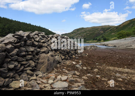 Haweswater, Cumbria UK. 19th July, 2018. Dry stone walls through the village of Mardale Green that was evacuated and flooded to make way for Haweswater Reservoir that was filled in the 1930's to aid drinking water to be pumped to Manchester over 80-miles away. The village was risen from the water after months of hot weather resulting in the low water levels. Pic taken 19/07/2018. Credit: Sam Holiday/Alamy Live News - Stock Photo
