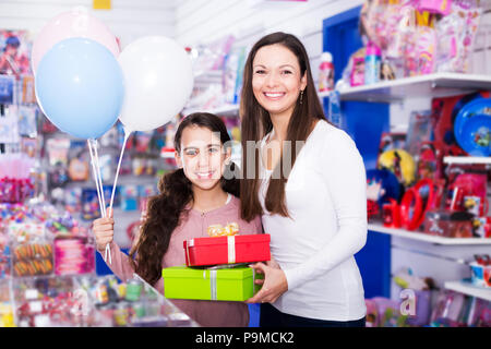 Portrait of happy mother and daughter holding gifts and balloons in shop - Stock Photo