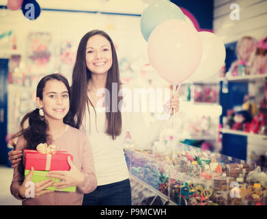 Portrait of cheerful mother and daughter holding gifts and balloons in store - Stock Photo
