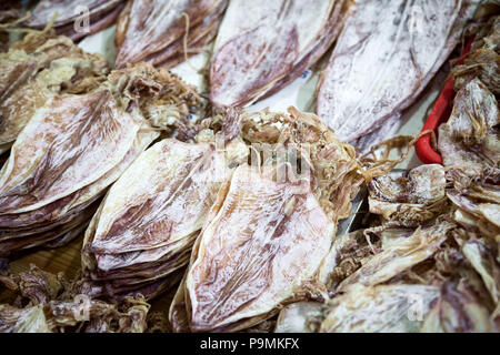 Many dried squids on a food market stall for sale. A lot of dry ready to eat cuttlefish snack background - Stock Photo