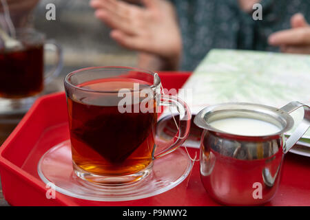Tea in a glass cup with a milk container, Poland. - Stock Photo