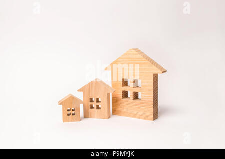 The concept of buying and selling real estate. Residential area, rental and investment in real estate. Three wooden houses stand in a row in descendin - Stock Photo