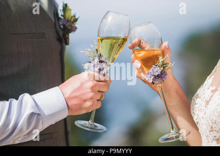 Man and woman hands holding two champagne glasses decorated with flowers for wedding ceremony - Stock Photo