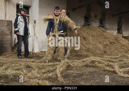 Traditional Easter procession known as Vodění Jidáše (Marching Judas) in the village of Stradouň in Pardubice Region, Czech Republic. Teenage boy Sebastian Talacko, who performs Judas this year, is being dressed by the villagers in a straw suit before the procession on 31 March 2018. Early in the morning on Holy Saturday, the eldest teenage boy in the village is dressed in a ridiculous straw suit. He is supposed to perform Judas Iscariot in this way. Wearing this obscure outfit, he has march through the village from house to house escorted by other boys, who twist wooden ratchets and sing a so - Stock Photo