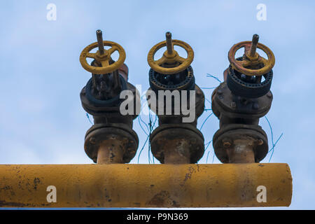 Three old iron pipe with valve, crane mechanism on sky background close-up - Stock Photo