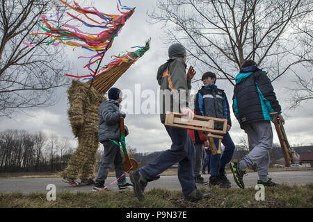 Traditional Easter procession known as Vodění Jidáše (Marching Judas) in the village of Stradouň in Pardubice Region, Czech Republic. A person dressed in a straw suit representing Judas marches through the village escorted with boys with ratchets during the procession on 31 March 2018. Early in the morning on Holy Saturday, the eldest teenage boy in the village is dressed in a ridiculous straw suit. He is supposed to perform Judas Iscariot in this way. Wearing this obscure outfit, he has march through the village from house to house escorted by other boys, who twist wooden ratchets and sing a  - Stock Photo