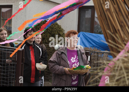 Traditional Easter procession known as Vodění Jidáše (Marching Judas) in the village of Stradouň in Pardubice Region, Czech Republic. Villagers with prepared donations in form of sweets and raw eggs pictured during the procession on 31 March 2018. Early in the morning on Holy Saturday, the eldest teenage boy in the village is dressed in a ridiculous straw suit. He is supposed to perform Judas Iscariot in this way. Wearing this obscure outfit, he has march through the village from house to house escorted by other boys, who twist wooden ratchets and sing a song about Judas, who betrayed his mast - Stock Photo