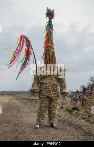 Traditional Easter procession known as Vodění Jidáše (Marching Judas) in the village of Stradouň in Pardubice Region, Czech Republic. A person dressed in a straw suit representing Judas is prepared to march through the village before the procession on 31 March 2018. Early in the morning on Holy Saturday, the eldest teenage boy in the village is dressed in a ridiculous straw suit. He is supposed to perform Judas Iscariot in this way. Wearing this obscure outfit, he has march through the village from house to house escorted by other boys, who twist wooden ratchets and sing a song about Judas, wh - Stock Photo