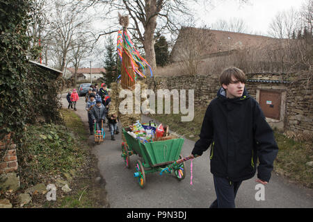 Traditional Easter procession known as Vodění Jidáše (Marching Judas) in the village of Stradouň in Pardubice Region, Czech Republic. A person dressed in a straw suit representing Judas marches through the village escorted with boys twisting ratchets and with a teenage boy who carries a cart for donations in the foreground during the procession on 31 March 2018. Early in the morning on Holy Saturday, the eldest teenage boy in the village is dressed in a ridiculous straw suit. He is supposed to perform Judas Iscariot in this way. Wearing this obscure outfit, he has march through the village fro - Stock Photo