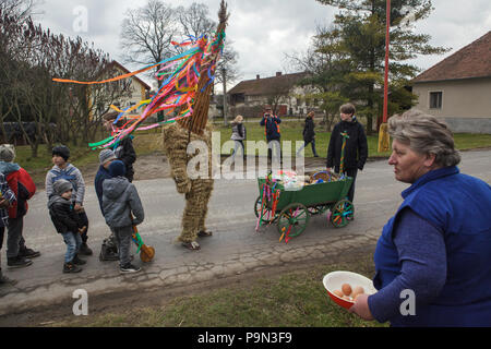Traditional Easter procession known as Vodění Jidáše (Marching Judas) in the village of Stradouň in Pardubice Region, Czech Republic. A person dressed in a straw suit representing Judas stops in front of the house escorted with boys with wooden ratchets and with a teenage boy who carries a cart for donations during the procession on 31 March 2018. The village woman with prepared raw eggs for donation is seen in the foreground. Early in the morning on Holy Saturday, the eldest teenage boy in the village is dressed in a ridiculous straw suit. He is supposed to perform Judas Iscariot in this way. - Stock Photo