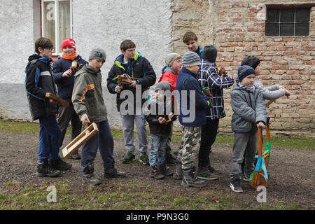 Traditional Easter procession known as Vodění Jidáše (Marching Judas) in the village of Stradouň in Pardubice Region, Czech Republic. Boys with wooden ratchets attend the procession on 31 March 2018. Early in the morning on Holy Saturday, the eldest teenage boy in the village is dressed in a ridiculous straw suit. He is supposed to perform Judas Iscariot in this way. Wearing this obscure outfit, he has march through the village from house to house escorted by other boys, who twist wooden ratchets and sing a song about Judas, who betrayed his master to the Jews, collecting sweets and eggs from  - Stock Photo