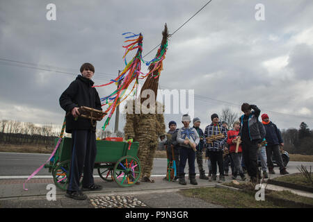 Traditional Easter procession known as Vodění Jidáše (Marching Judas) in the village of Stradouň in Pardubice Region, Czech Republic. A person dressed in a straw suit representing Judas stops in front of a house escorted with boys twisting wooden ratchets and with a teenage boy who carries a cart for donations during the procession on 31 March 2018. Early in the morning on Holy Saturday, the eldest teenage boy in the village is dressed in a ridiculous straw suit. He is supposed to perform Judas Iscariot in this way. Wearing this obscure outfit, he has march through the village from house to ho - Stock Photo