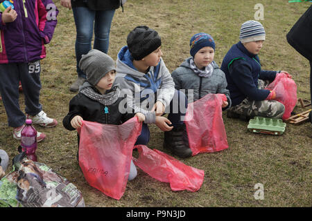 Traditional Easter procession known as Vodění Jidáše (Marching Judas) in the village of Stradouň in Pardubice Region, Czech Republic. Boys wait with empty plastic bags for their portions of sweets collected during the procession on 31 March 2018. Early in the morning on Holy Saturday, the eldest teenage boy in the village is dressed in a ridiculous straw suit. He is supposed to perform Judas Iscariot in this way. Wearing this obscure outfit, he has march through the village from house to house escorted by other boys, who twist wooden ratchets and sing a song about Judas, who betrayed his maste - Stock Photo
