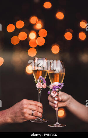 Two glasses of champagne in couple hands decorated with fresh flowers and light orange glare on background - Stock Photo