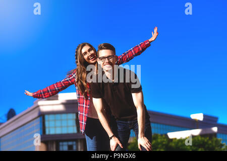 Outdoor shot of man giving woman piggyback. Man carrying woman oh his back - Stock Photo