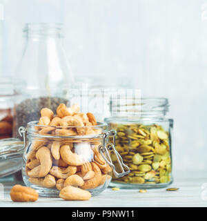 Various nuts and seeds in glass jars over white wooden table against white background. The concept of vegetarian and organic food. - Stock Photo