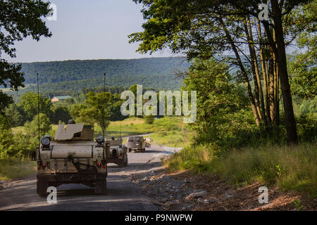 New York Army National Guard Soldiers with the 105th Military Police Company, 102nd Military Police Battalion, New York Army National Guard, conduct a security detail training exercise during their annual training at Fort Indiantown Gap, P.A. on July 16, 2018. More than 370 New York Army National Guard Soldiers from military police, engineer and transportation companies used this year's three weeks of summer training and the improved multi-million dollar facilities at Fort Indiantown Gap to hone their skills in July 2018 (U.S. Army National Guard photo by Spc. Amouris Coss) - Stock Photo