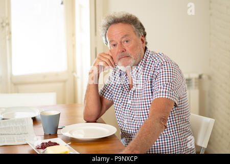Portrait of depressed senior old man with grey hair reading the newspaper while having breakfast and drinking a coffee in old age retirement concept. - Stock Photo
