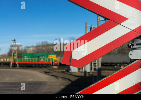 Warning signs at railway crossing with a diesel train and blue skies. Riga, Latvia - Stock Photo