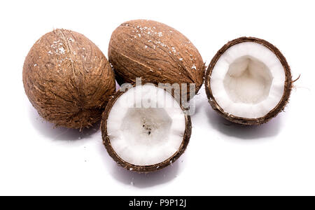 Two whole coconuts and two cracked coconut halves isolated on white background - Stock Photo