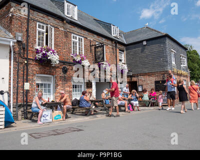 Tourists and customers sitting outside the Shipwrights Arms out on a hot summer day at Padstow Harbour Cornwall UK - Stock Photo