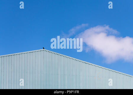 An abstract image of a metal building against a blue sky with clouds with a crow sitting on it in Padstow Cornwall UK - Stock Photo