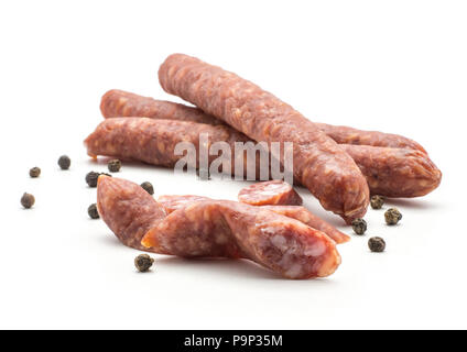 Three Hungarian dry sausages pepperoni with black pepper and cut pieces isolated on white background smoked in natural casing mixed pork and beef - Stock Photo