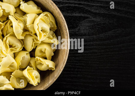 Raw tortellini pasta in a wooden bowl flatlay on black wood background Italian traditional dumpling - Stock Photo