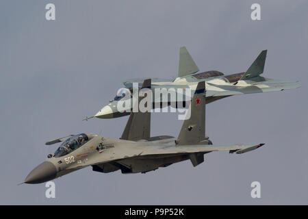 Sukhoi T-50 and Sukhoi Su-30MK jet fighters of Russian Air Force fly in formation at MAKS-2013 International Airshow near Zhukovsky, Russia - Stock Photo