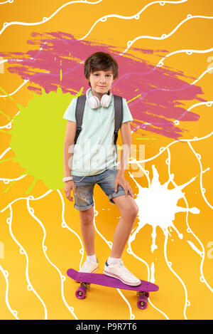Confident boy putting his foot on a skateboard and smiling - Stock Photo