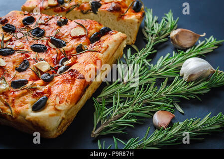 traditional italian homemade focaccia with olives and rosemary on a dark background - Stock Photo