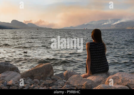 Girl sits by lakeshore at Marine Park in Penticton watching multiple lightening sparked wildfires in South Okanagan - Stock Photo