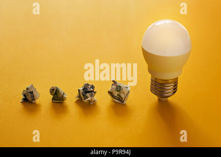 concept of energy saving. Lamp and crumpled dollar bills in a row on yellow background - Stock Photo