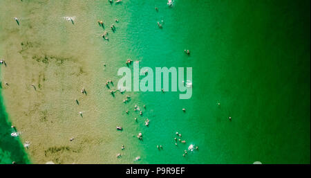 Aerial View From Flying Drone Of People Crowd Having Fun, Playing And Relaxing In Water At The Black Sea In Romania - Stock Photo