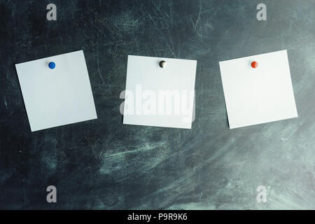 Three white stickers on dark board pinned with colored studs - Stock Photo