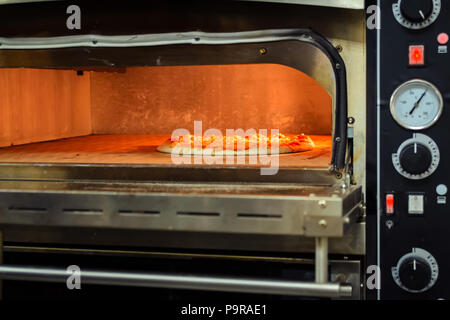 Cooking pizza in an electric oven in a restaurant, close up - Stock Photo