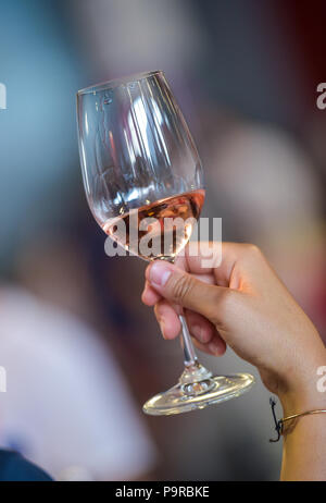 Women hand with a glass of rose wine - Stock Photo