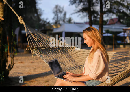 Businesswoman working with laptop and sitting on sand in wicker hammock. - Stock Photo