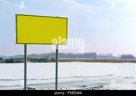 yellow warning sign, signpost stand on the road in winter - Stock Photo