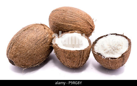 Two whole coconuts and two cracked coconut halves with shavings isolated on white background - Stock Photo