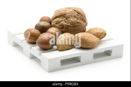 Nuts mix (walnut, hazelnut and almond) on a pallet isolated on white background - Stock Photo