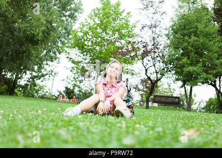 Happy teenager girl sitting on the grass in the park next to her bicycle - Stock Photo