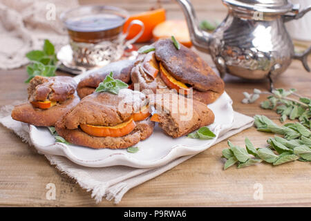 Homemade pastries with persimmons, for breakfast. Beautiful glass with tea. Kettle. A wooden table, a place for text or advertising - Stock Photo