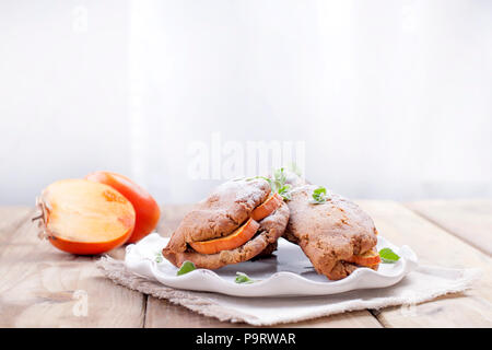 Homemade pastries with fresh persimmons, for breakfast, white plate on a napkin. Wooden table. Free space for text or advertising - Stock Photo