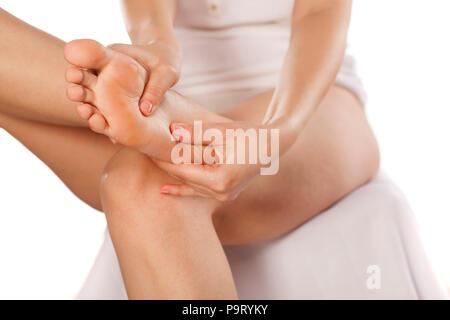 woman massaging her tired feet - Stock Photo