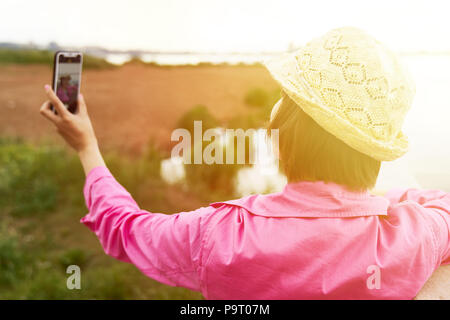 Girl in pink coat and yellow hat is taking selfie on nature. - Stock Photo
