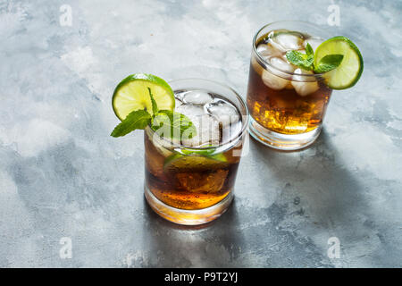 Rum and cola Cuba Libre drink with lime and ice on rustic concrete table - Stock Photo
