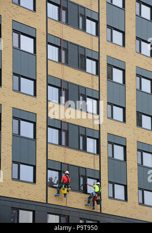 Two window cleaners use abseiling ropes to access windows on a new tower block in Portsmouth town centre, Hampshire, UK - Stock Photo